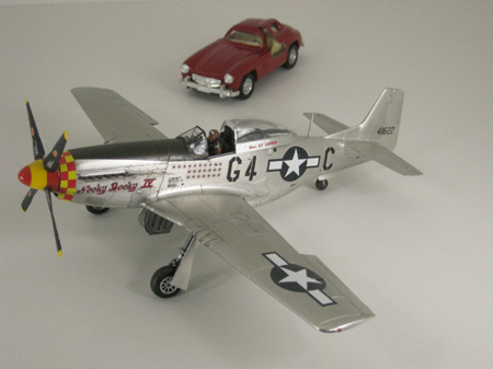 studio light photo of P-51D Mustang airplane and Mercedes Benz car